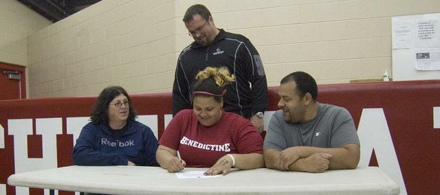 Tonganoxie High senior Domino Grizzle, center, signs a letter of intent with the Benedictine College track team on April 18 at THS. Seated beside Grizzle are her mother, Beth, and father, James. Standing behind them is BC track coach Darin Schmitz.