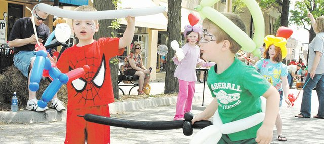 Twin brothers Michael Fandel, left, and William Fandel, both 3 years old, fight each other with balloons. In the fight, Michael was Spiderman and William was the sword-wielding villain.