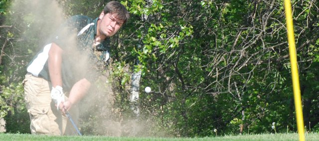 Basehor-Linwood's Caleb Johnson chips out of the sand trap on No. 9 at Sunflower Hills Golf Course at the Kaw Valley League Championships.
