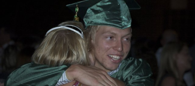 Basehor-Linwood High School graduate Austin Laing hugs his aunt, Karla Kahmeyer, outside the school after its 2011 commencement ceremony. Laing plans to head to the University of Arkansas in the fall, he said.