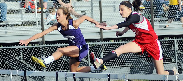 Baldwin High School senior Lyndsey Lober, left, runs neck-and-neck with Osawatomie's Tayler Soucie during the 100-meter hurdles finals Friday. Lober narrowly won the race. Her time of 15.0 seconds tied the BHS school record set by Jenny Cook in 1996.