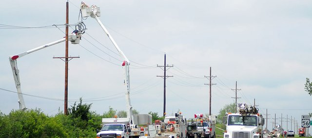 Crews repair power lines on U.S. Highway 56 just west of the Kansas Highway 33 intersection, Thursday, May 12, 2011. U.S. Highway 56 was closed Wednesday night after a thunderstorm knocked down power lines near the road. One lane of the highway reopened late Thursday morning.