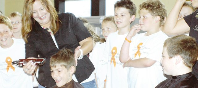 Cole Vlack, a Sacred Heart fourth-grader, awaits his head being shaved while classmate Peter Merrell (right) does the same. The two were among five students to volunteer their hair in support of Garett Barraza, a classmate with cancer.