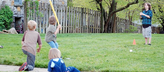 A Baldwin City family plays baseball outside in the yard they share with a Greek sorority from Baker University.