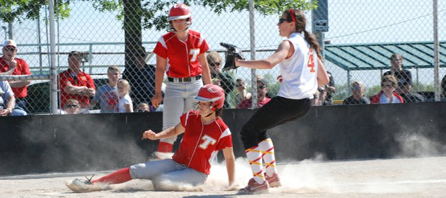 Tonganoxie High senior Kaitlyn Wolken slides home to score a run against Atchison in a regional semifinal victory on May 17 at Field of Dreams.