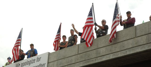Members of the Tonganoxie American Legion Post 41 Riders wait Monday on the Leavenworth County Road 1 overpass above Interstate 70 to greet an expected 600 motorcyclists headed to Washington, D.C., for a Memorial Day Weekend rally. The American Legion Riders keep busy riding to funerals, homecomings and other activities to honor veterans