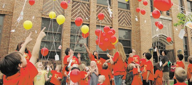 "McDanield Early Childhood Center teachers, students and other well-wishers launch balloons toward the heaves in honor of ""Miss Kim"" Wendt, a former teacher's aide at the center. Wendt died in April shortly after being diagnosed with cancer. The launch Friday outside the center honored Wendt's memory."