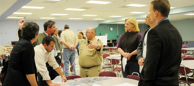 Brian Austin, left, Bartlett and West engineer, talks with Baldwin City patrons at the North Sixth Street Project meeting on April 28. Austin was at Tuesday's city council meeting to discuss the project.