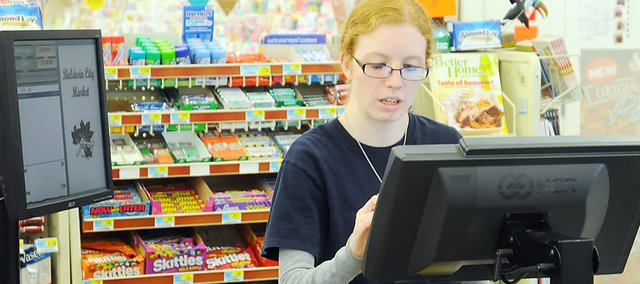 Katlyn Pratt, who is from Baldwin City and attends Johnson County Community College, works at the checkout counter May 31 at the Baldwin City Market.