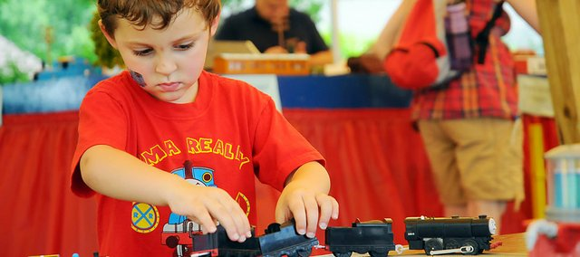 Nicholas Cone, 3, plays with one of the toy trains under the Imagination Station tent Friday. He visited the Baldwin City event for the third time with his parents, John and Lauren Cone of Kansas City, Mo. The annual A Day Out With Thomas ends Sunday afternoon at the Midland Depot in Baldwin City.