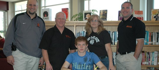Caleb Seaton, seated, will wrestle in college at Fort Hays State University. Joining the Bonner Springs High School senior at his signing ceremony are, standing, from left: BSHS Activities Director John Hilton, father and BSHS assistant coach Jerry Seaton, mother Cheryle Seaton, and BSHS coach Brandon Jobe.