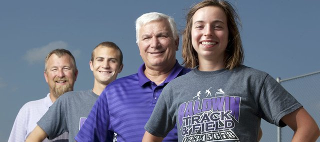 Baldwin High School sophomore Kaitlyn Barnes, right, is pictured with girls track coach Ted Zuzzio, junior Brian Wright and boys track coach Mike Spielman on Monday at Baldwin High. The Bulldogs won state titles this past year in boys and girls track & field, along with boys and girls cross country. They became the first school in Kansas history to sweep both state titles in the same school year.