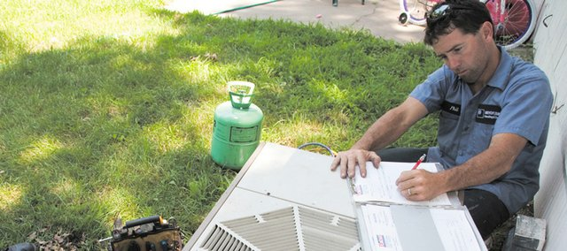 Air conditioning technician Phil Foster fills out paperwork after servicing a unit.  Bruce Snead,a K-State Research and Extensionresidential energy specialist, answers questions about how to help keep the lid on cooling costs.