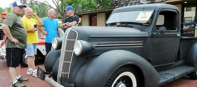Baldwin City resident Daryl Rockers chats with friends as they stand around his 1936 half-ton Dodge truck during the car show Saturday.