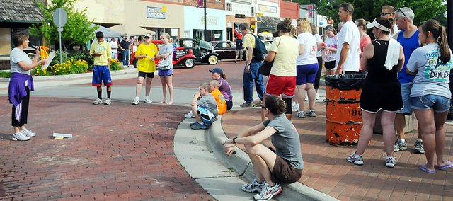 Baldwin City's Cheryl McCrary, left, reads the results of the Walking on Sunshine 5K run/walk Saturday morning in downtown Baldwin City. There were 68 runners and walkers in the annual event, which was in conjunction with Planes, Trains and Automobiles.