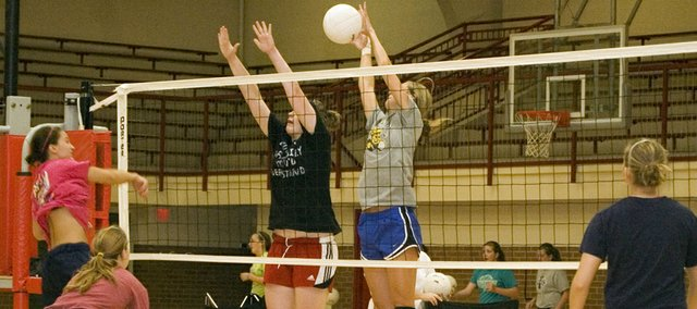 Brooklyn Kerbaugh, far right, elevates for a block, with Katelyn Waldeier beside her, following a spike by Hannah Kemp on Thursday at Tonganoxie High volleyball camp. THS had its four-day summer camp June 20-23.