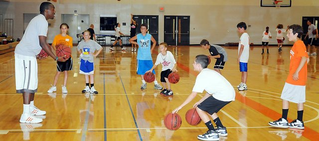 Baker University basketball campers practice their dribbling during Tuesday's afternoon session. This year is coach Brett Ballard's second annual camp.