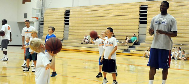 Kansas University basketball player Thomas Robinson receives a pass from Ryker Grossner during Thursday's Brett Ballard Basketball Camp in Collins Center. Grossner, the son of Baker head football coach Mike Grossner, was one of about 65 campers who spent the final day of the camp with Robinson and KU incoming freshman Ben McLemore.