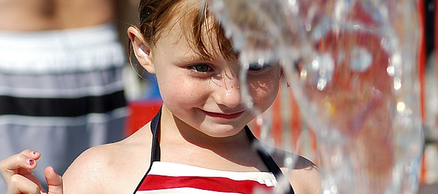 Bianca Willeford Brown, 4, Shawnee plays in a water feature at the Thomas A. Soetaert Aquatic Center. Temperatures were close to 100 degrees Friday afternoon, when Shawnee pools celebrated Freedom Fling with contests and prizes for kids.