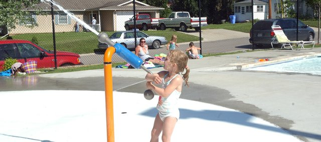 Four-year-old Ella Bain blasts away Friday on the water cannon at the Tonganoxie Water Park as temperature headed to near triple-digits. Pool manager Darrin Shupe credits the pool's many features designed to appeal to different age groups as one of the factors in its continuing popularity.