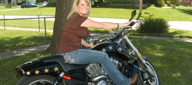 Country music artist Joey Glenn sits on a Harley Davidson motorcycle that will be raffled off as a fundraiser for Flowers for Heroes, a non-profit organization with a mission to place flowers at the bases of veterans' headstones at national cemetery. Glenn agreed to support the organization because of her family ties to the military.