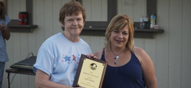 Basehor resident Judy Goens (left) receives the Basehor Chamber of Commerce Outstanding Citizen Award, presented by chamber vice president Deb Taylor, at the Basehor Fourth of July celebration Monday at Basehor-Linwood High School.