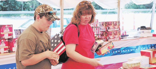 Lori Peterson and her son, Paul Peterson III, of Bonner Springs, check out the fireworks stand in downtown Bonner Springs on the Fourth of July.