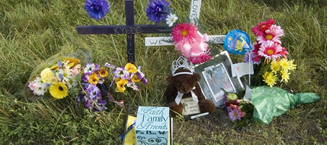 Flowers and crosses are among the items placed near the crash site of a rollover accident on U.S. Highway 24-40 east of 150th Street. Tonganoxie High School student Kylee Wilson was killed in a rollover accident there Thursday.