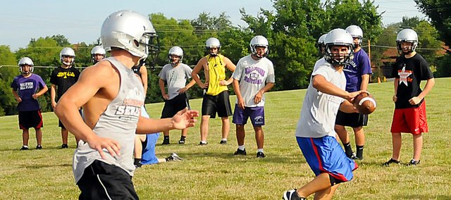 Baldwin High School senior Jake Mindez pitches the ball to senior Clayton Duncan during an offensive drill at camp Tuesday. The Bulldogs started their annual week of camp Monday morning.