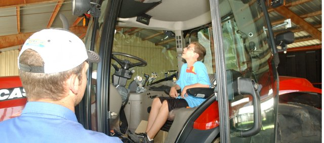 Reno Bobwhite 4-H member Ahren Gann, 10, checks out the air-conditioned cab of a tractor provided for the 4-H club's annual safety day while Gabe Gantz of Kansas Equipment Inc. of Wamego informs him of its finer points. Gantz was one of several out-of-town presenters recruited for the safety day.