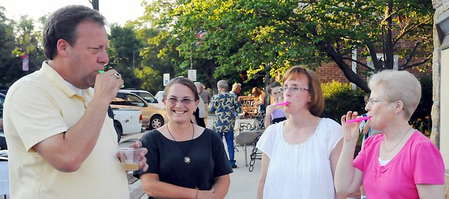 State Sen. Tom Holland leads Becky Henderson, second from right, and Jan Boyd, far right, in a kazoo performance as Sue Stark watches at Friday's Art Walk.The event, which featured ice cream and a cupcake contest drew a good crowd downtown despite triple-digit temperatures.