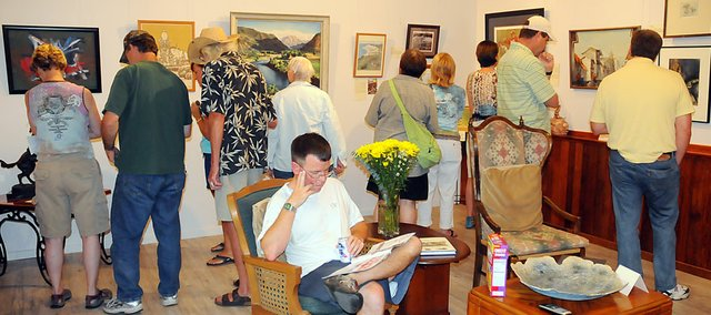 Baldwin City resident Joe Bathke, center, sat inside the Lumberyard Arts Center exhibit opening as part of the exhibit. The opening was a bit hit Friday.