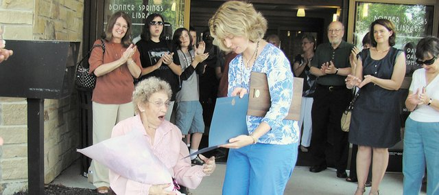 A surprised Edna Stewart is presented with the first-ever Friend of the Year Award by Kim Beets, Bonner Springs City Library director. The award was presented as part of the library's two-year anniversary event.