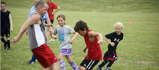 "Charlie Gilmore and Tristen Briley converge on the ball during a kids vs. parents game on Friday morning, the last day of Tonganoxie High youth ""Sokker Kamp."""