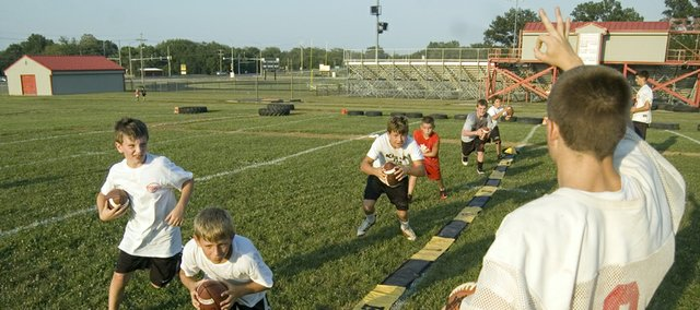 A group of quarterbacks at Tonganoxie High youth football camp look toward THS quarterback Garret Elston for their next move while running through drills on Thursday outside Beatty Field. Roughly 120 fourth- through eighth-grade players attended camp from Wednesday, July 27 through Friday.