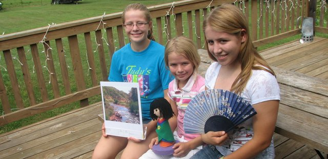 Casey (from left), Amy and Katie Eberth display mementos from their 4-H experiences. Casey held a photography entry, Amy a foam Japanese doll she made for an arts and crafts entry and Katie a fan she bought while in Japan through a 4-H exchange program.