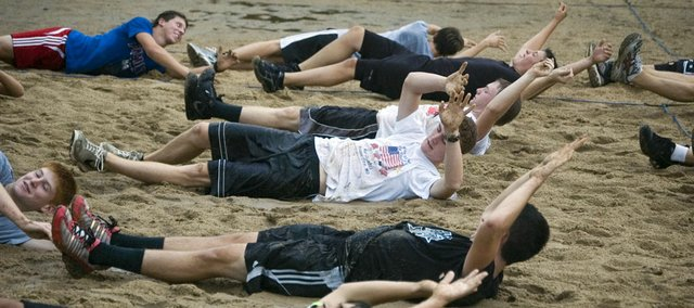 Tonganoxie High soccer players roll over in the wet sand at Chieftain Park Monday morning during their first practice of the preseason. Heavy rain Monday morning altered the practice plans of both the THS boys soccer and football teams.