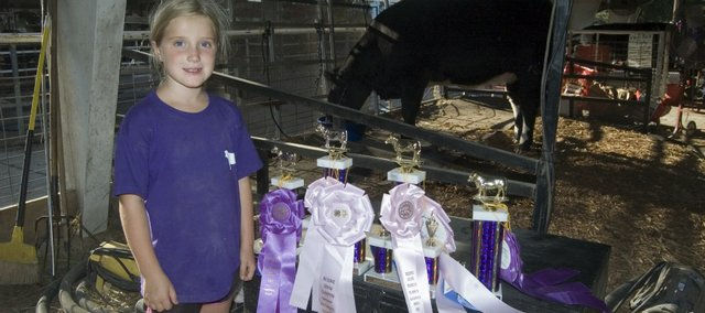 Abby Wood, 8, with her trophies at the Leavenworth County Fair. Abby won reserve champion in market steer in her first year.
