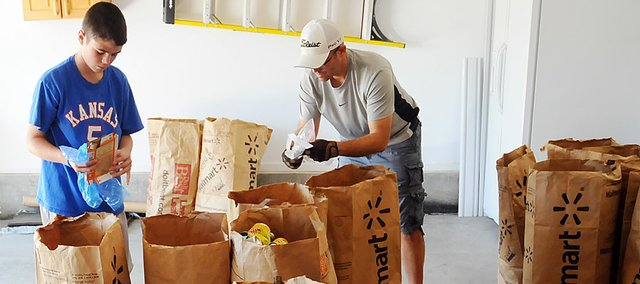 Jackson Barth, left, and father Doug Barth sort through recycling Sunday in their garage in Baldwin City. Jackson is the founder of 2 Kids and a Mom Recycling, which he created four years ago. Jackson donates money earned from the business to St. Jude Children's Research Hospital and has donated around $900 to the charity in four years.