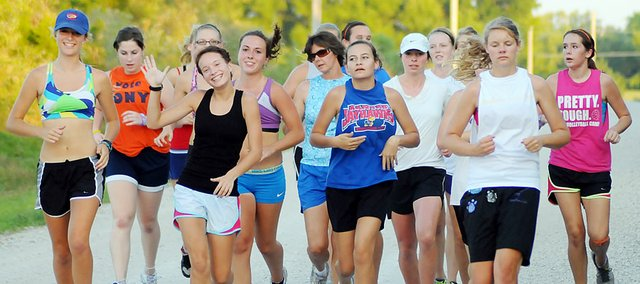 Members of the Baldwin High School girls' cross country team run on a gravel road during practice Tuesday evening. The BHS girls' squad has 29 runners this fall.