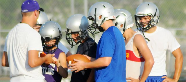 Baldwin High School assistant football coach Austin Inzer, left, shows several players a diagram of the play they are about to run at practice Tuesday evening. The Bulldogs have practiced well during the opening days of the season, which began Monday morning.