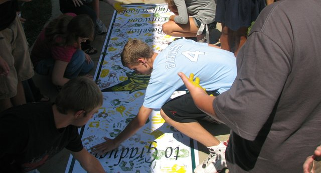 "Freshmen place their handprints on the ""Commitment to Graduate"" banner, as others hold their paint-covered palms away from their bodies as they wait their turn. This year's freshman class at BLHS numbers 162 students, assistant principal Jarred Fuhrman said."