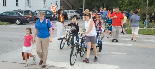 Crossguard Christy Angell stops traffic the morning of Tuesday, Aug. 23, 2011, on Fourth Street as parents and children head to the first day school at Tonganoxie Elementary School.