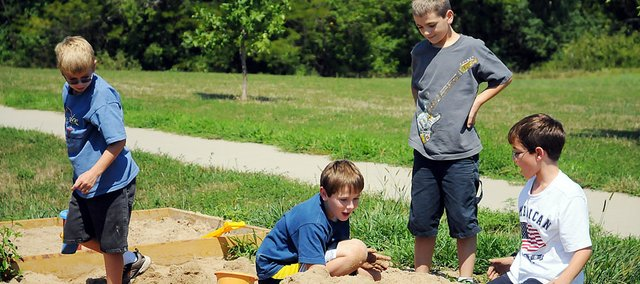 Four Baldwin Elementary School Intermediate Center fifth-graders play together in the sandbox at recess during the second full-day of school Friday. They are, from left, James Foster, Max Gilliland, Lyle Story and James Lock. All USD 348 students began classes last Thursday, Aug. 18.