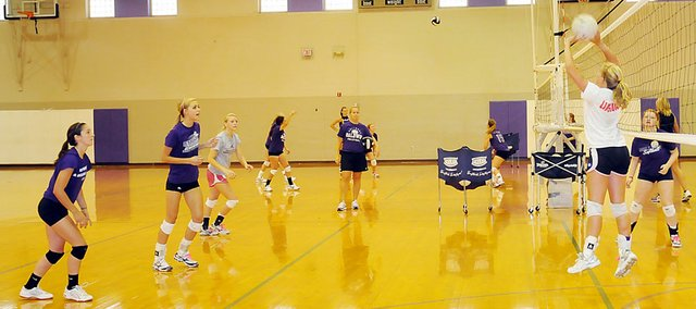 Baldwin High School junior Katie Pattrick, right, sets the ball to teammates during a drill at practice last week. The BHS volleyball squad is aiming to finish the fall with a winning record after finishing 2010 with a 17-20 record.