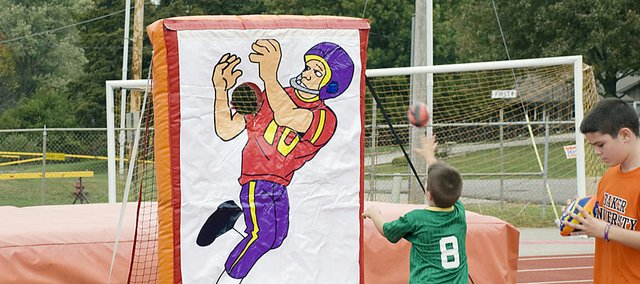 Young Wildcat football fans participate in a football toss game at the KidZone last fall. The KidZone will return during homecoming activities on Oct. 22.
