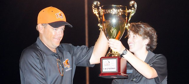 Baker University football coach Mike Grossner accepts the Victory Sports First Down Classic trophy from Baker Athletics Director Theresa Yetmar after Saturday's 41-16 victory over Ottawa University.