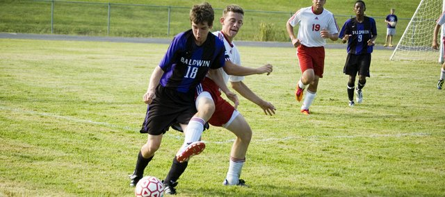 Tonganoxie High senior defender Marcus Titterington battles Baldwin's Alec Petry for the ball near the sideline in the second half Friday. The Chieftains tied BHS, 1-1, in their season opener.