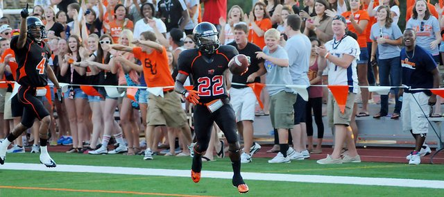 Baker University's Reggie Harris (No. 22) celebrates a touchdown in the endzone near the Wildcats' student section Saturday night at Liston Stadium. Harris returned a punt for a score to help Baker beat Ottawa 41-16.