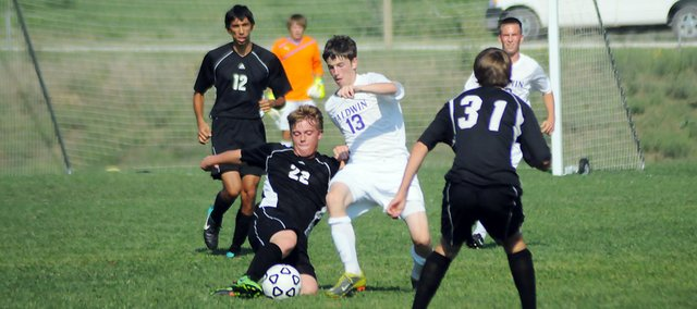 Baldwin High School sophomore Duncan Murray (No. 13) battles a Paola defender for a loose ball during the first half of Tuesday's contest. Baldwin won the game 3-0.